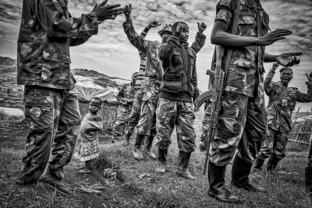 Nyatura soldiers dancing before another day of patrol around Mudere mine. They control every aspect of life in Rubaya: without any payment from the central government, they live by costant oppression on the civilian population, with abuse of power, theft, rapes and executions.