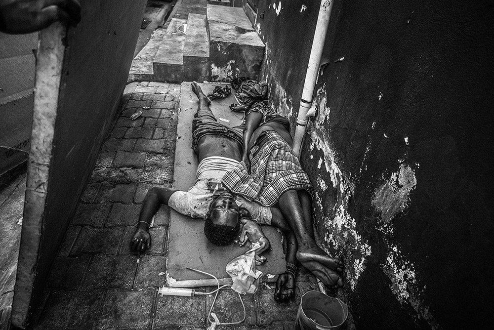 'CITY MORGUE OVERFLOW' - PORT-AU-PRINCE, HAITI. MAY 7, 2015. A man, a woman and her baby lie dead next to a wall outside the city morgue. They were lying behind a wooden board that when pulled back revealed the bodies. I was told by morgue workers close-by that continual power cuts (corpse refrigeration) and lack of city funds for proper disposal meant that bodies would be stored crudely until family members came to claim the bodies. In many case however, bodies were left unclaimed so were buried in mass graves later. Haitian culture prevents cremation.