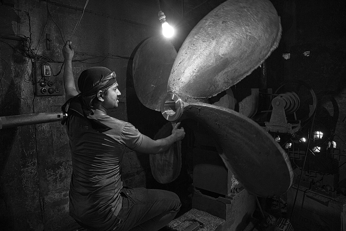 A man working on a new propeller inside his small shop, near the ship breaking- rebuilding on Buriganga river. The whole south shore of the river is full of craft workshops where each piece is repaired or produced again.