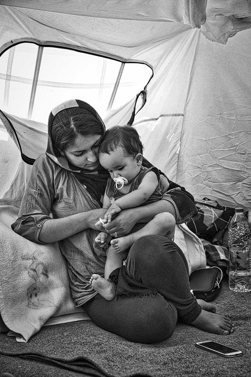 A young Afghan mother play with her baby inside a tent in Pireo Harbour (Athens, Greece). I don't know her name: when I had shot this photo, the intensity of their relation was so powerful, a unique treasure inside desolation of refugee camp, that I preferred don't break the magic of the moment (and write the name). She walked all the way, from Kabul to Istanbul, when she was pregnant: two months of fear, risks, crossing mountains and hiding during the nights. They waiting for a new life.