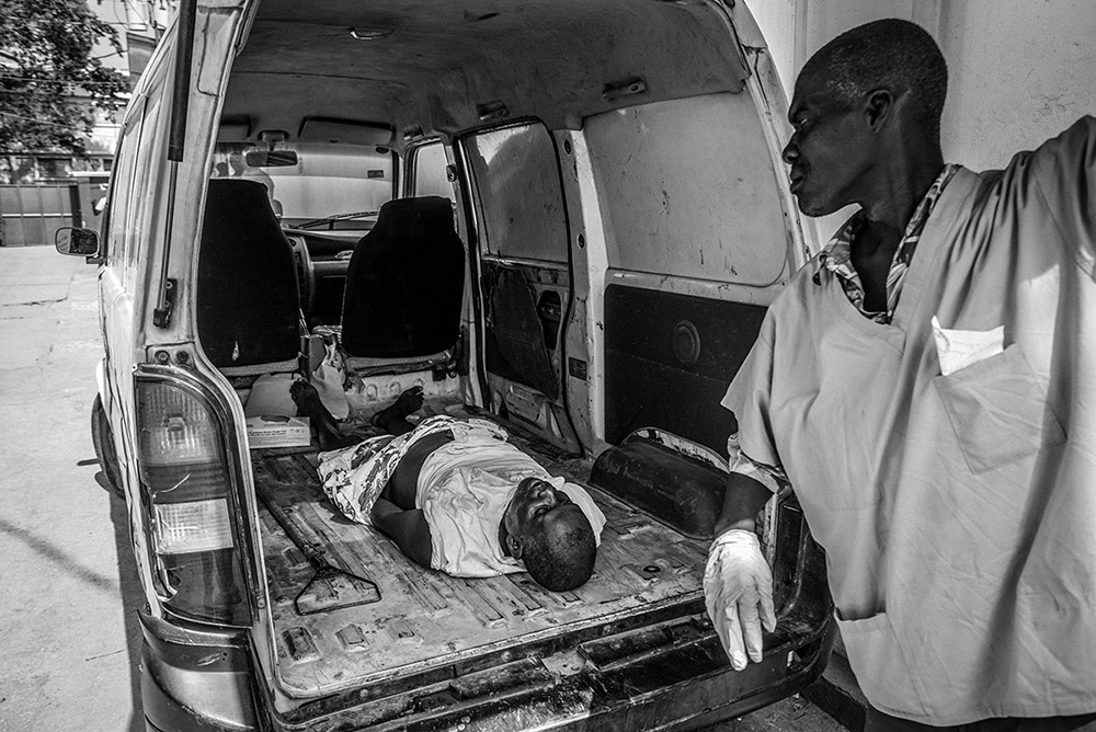 'MORGUE ARRIVAL' - PORT-AU-PRINCE, HAITI. MAY 7, 2015. A morgue worker opens the back of a van after having picked up a body from an undisclosed location. The dead man's arms were tucked inside his shorts while he was moved from his place of death to the mortuary.
