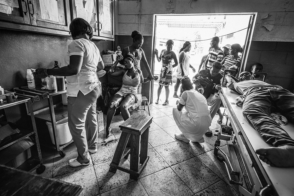 'NURSING HURRICANE MATTHEW'S WOUNDED' - LES CAYES, HAITI. OCTOBER 15, 2016. The interior of a busy medical center in downtown Les Cayes where nurses tend to some of those injured by Hurricane Matthew. Family members and relatives wait by the door. The town of Les Cayes was the first place to be hit by the Category 4 storm that barreled through the area on October 2016.