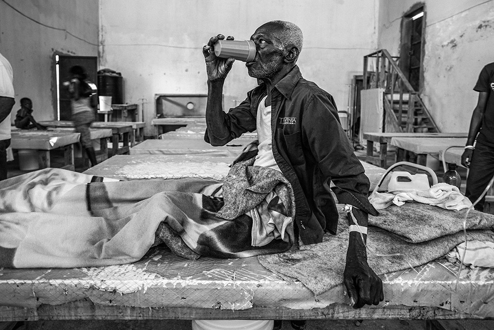 'CHOLERA RECOVERY' - CARREFORE, HAITI. JANUARY 14, 2015. At Cholera Treatment Center (CTC) in one of Port-Au-Prince's coastal outskirts, an elderly man gulps water for rehydration. According to the World Health Organization, children and the elderly are proven to be the most susceptible to cholera.