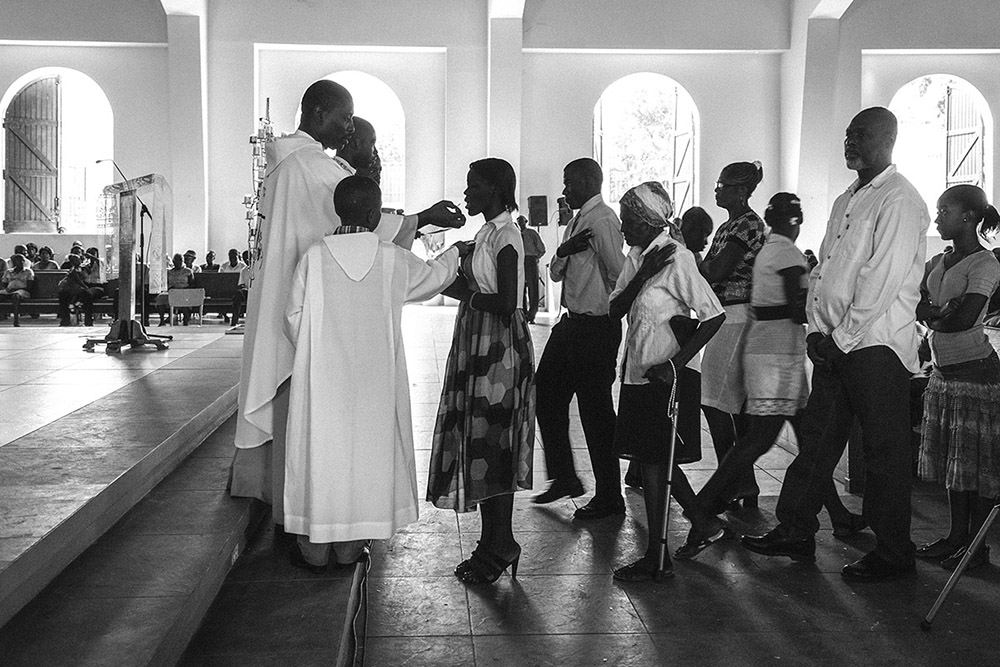 'HOLY COMMUNION' - PORT-AU-PRINCE, HAITI. JANUARY 11, 2015. Churchgoers attend a 5th earthquake anniversary service in the newly-built annex that lies directly next door to the crumbled ruins of the The Cathedral of Our Lady of the Assumption.