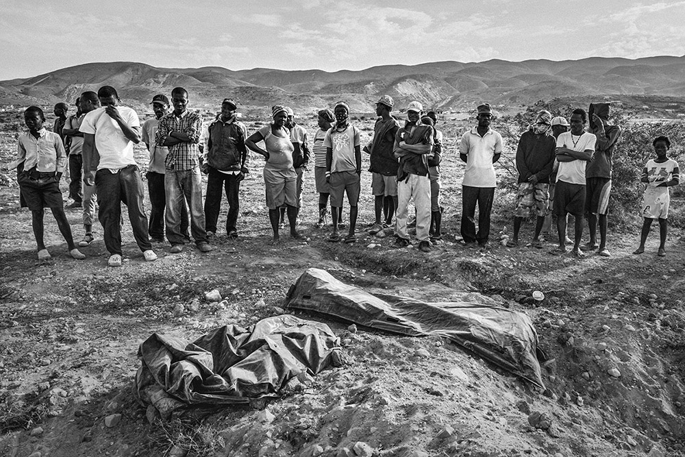 'UNMARKED SHALLOW GRAVES' - PORT-AU-PRINCE, HAITI. MAY 7, 2015. In the hills of Titanyen, some 10 km outside of Port-Au-Prince, lie the crudely wrapped bodies that were illegally deposited in mass graves by health officials using private contracted disposal companies. When the local residents tried to stop the late night dumping of these bodies, they were dispersed by the Haitian national police with tear gas just a few days before this image was taken. In a twist of grim irony, many of these residents who had moved from the earthquake rubble to these peaceful hills five years earlier, were now being confronted with the morbid hell from which they escaped.
