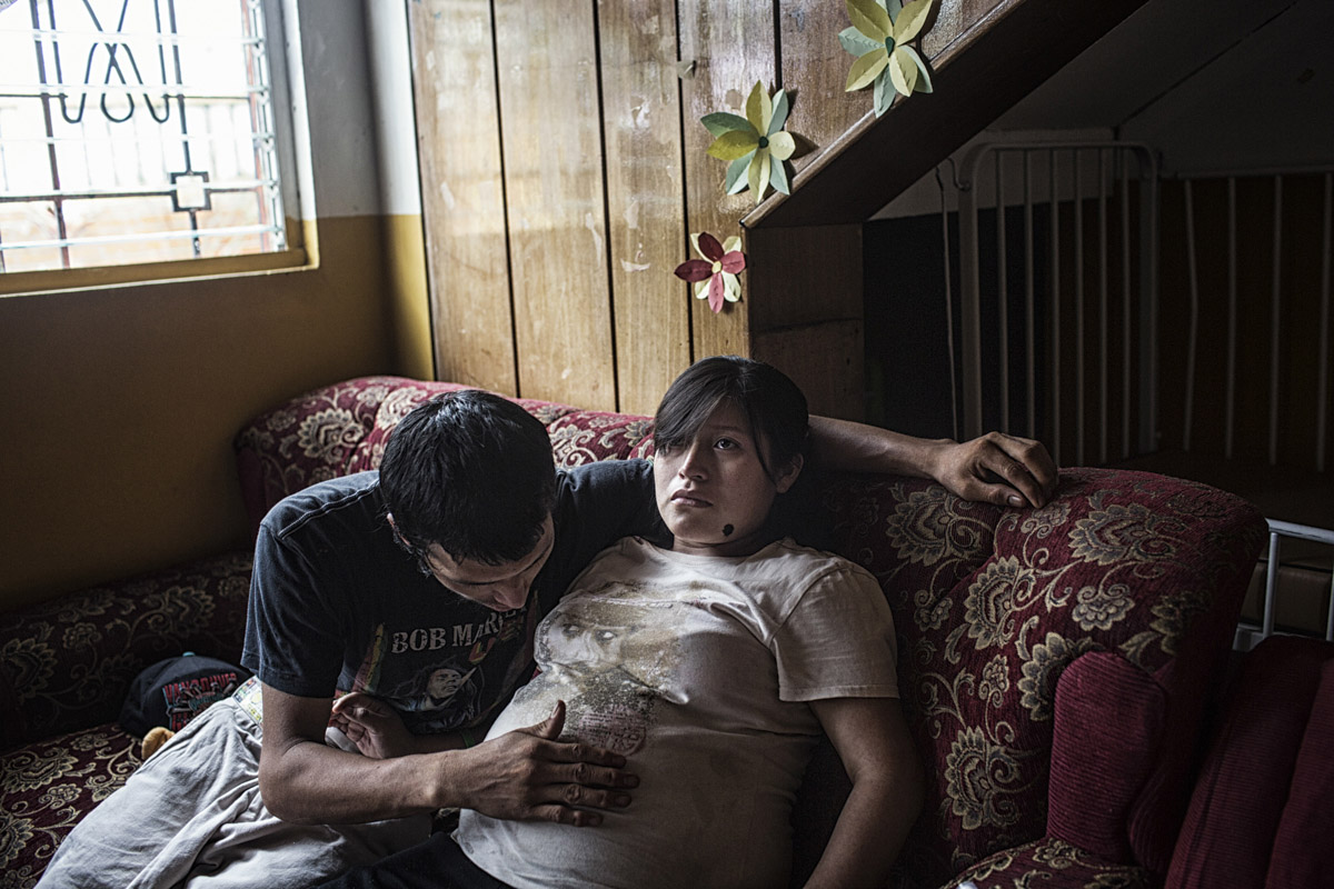 Planes de Renderos, El Salvador-May 2016: Idalia Alverado Sanchez and her husband Alex in an intimate moment awaiting the arrival of their first child together at the maternal waiting house which especially help women who come from areas without access to a nearby hospital wait out the end of the pregnancies in order to be close to a hospital and avoid complications. This is 21 year old Idalia's 3rd child, the first of which she had when she was 13. Pregnant women in today's El Salvador face a whole host of challenges from the threat of the mosquito born illness, Zika which has been linked to the grave condition of microcephaly in newborns, to the constant threat of gang violence with one of the highest murder rates in the world, to an increasing rape epidemic. However the most important threat to women's reproductive rights is by far the State's criminal ban on abortion. Doctors and nurses are trained to spy on women's uteruses in public hospitals, reporting any suspicious alteration to the authorities and provoking criminal charges which can lead to between 6 months to 7 years in prison. It is the poorer class of women who suffer the most as doctors in private hospitals are not required to report. Roughly 25 women are serving 30 to 40 year sentences on homicide charges for allegedly killing their newborn children. Although the women's stories, most of which resemble premature births or late term miscarigaes are often dismissed in trials, laced with moral accusations, based little on the consitution and scientific facts. ©Nadia Shira Cohen