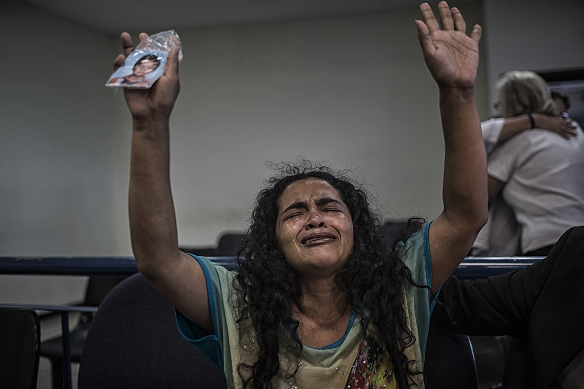 "San Salvador, El Salvador-May 2016: Maria Teresa Rivera reacts to her sentence annulement in Federal Court, chanting ""Dios Existe"" with a photo of her son, Oscar in her hand. The Supreme Court annulled María Teresa Rivera's 40 year sentence for aggravated homicide of her prematurely born infant after she had already served 4 years in jail, barely able to see her son who was being taken care of by her ill mother in a violent gang controlled neighborhood. After a careful review of the medical evidence and all the facts the judge stipulated that there was not enough proof of evidence that she intentially killed her child and ordered that reparations be made to her for her time served. Pregnant women in today's El Salvador face a whole host of challenges from the threat of the mosquito born illness, Zika which has been linked to the grave condition of microcephaly in newborns, to the constant threat of gang violence with one of the highest murder rates in the world, to an increasing rape epidemic. However the most important threat to women's reproductive rights is by far the State's criminal ban on abortion. Doctors and nurses are trained to spy on women's uteruses in public hospitals, reporting any suspicious alteration to the authorities and provoking criminal charges which can lead to between 6 months to 7 years in prison. It is the poorer class of women who suffer the most as doctors in private hospitals are not required to report. Roughly 25 women are serving 30 to 40 year sentences on homicide charges for allegedly killing their newborn children. Although the women's stories, most of which resemble premature births or late term miscarigaes are often dismissed in trials, laced with moral accusations, based little on the consitution and scientific facts. ©Nadia Shira Cohen"
