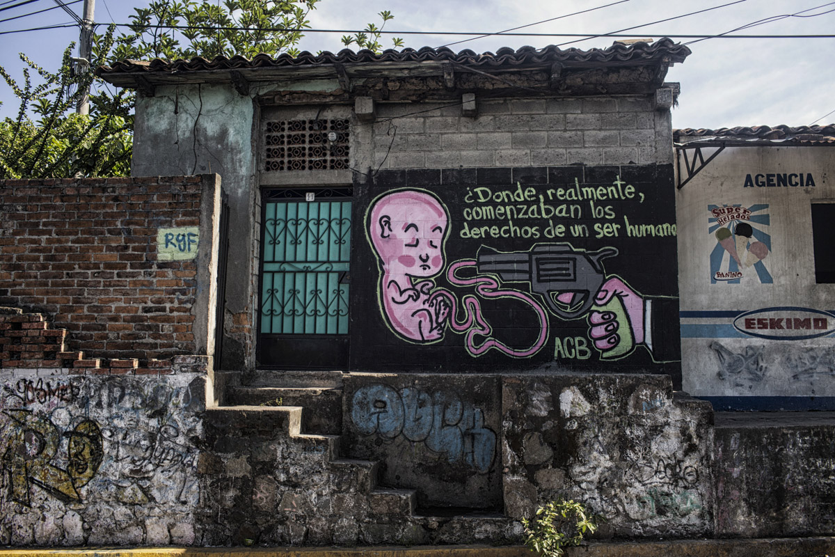 San Salvador, El Salvador-May 2016: A pro life wall mural adorns the wall in a side street on the main highway from Chalatenango to San Salvador. The society has over time embraced the abortion ban for the most part. Pregnant women in today's El Salvador face a whole host of challenges from the threat of the mosquito born illness, Zika which has been linked to the grave condition of microcephaly in newborns, to the constant threat of gang violence with one of the highest murder rates in the world, to an increasing rape epidemic. However the most important threat to women's reproductive rights is by far the State's criminal ban on abortion. Doctors and nurses are trained to spy on women's uteruses in public hospitals, reporting any suspicious alteration to the authorities and provoking criminal charges which can lead to between 6 months to 7 years in prison. It is the poorer class of women who suffer the most as doctors in private hospitals are not required to report. Roughly 25 women are serving 30 to 40 year sentences on homicide charges for allegedly killing their newborn children. Although the women's stories, most of which resemble premature births or late term miscarigaes are often dismissed in trials, laced with moral accusations, based little on the consitution and scientific facts. ©Nadia Shira Cohen