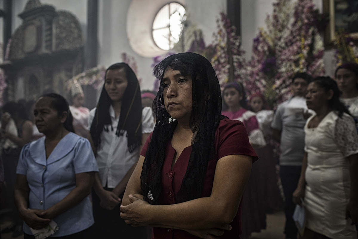 Panchmalco, El Salvador-May 2016: Churchgoers pay tribut to the Virgin Mary at a mass as part of the annual Palms Festival features a procession of the Virgin Mary through the town's narrow streets and attracts people from all over the country as well as internationally who come to idolize her. Pregnant women in today's El Salvador face a whole host of challenges from the threat of the mosquito born illness, Zika which has been linked to the grave condition of microcephaly in newborns, to the constant threat of gang violence with one of the highest murder rates in the world, to an increasing rape epidemic. However the most important threat to women's reproductive rights is by far the State's criminal ban on abortion. Doctors and nurses are trained to spy on women's uteruses in public hospitals, reporting any suspicious alteration to the authorities and provoking criminal charges which can lead to between 6 months to 7 years in prison. It is the poorer class of women who suffer the most as doctors in private hospitals are not required to report. Roughly 25 women are serving 30 to 40 year sentences on homicide charges for allegedly killing their newborn children. Although the women's stories, most of which resemble premature births or late term miscarigaes are often dismissed in trials, laced with moral accusations, based little on the consitution and scientific facts. ©Nadia Shira Cohen as part of the annual Palms Festival features a procession of the Virgin Mary through the town's narrow streets and attracts people from all over the country as well as internationally who come to idolize her. Pregnant women in today's El Salvador face a whole host of challenges from the threat of the mosquito born illness, Zika which has been linked to the grave condition of microcephaly in newborns, to the constant threat of gang violence with one of the highest murder rates in the world, to an increasing rape epidemic. However the most important threat to women's reproductive righ