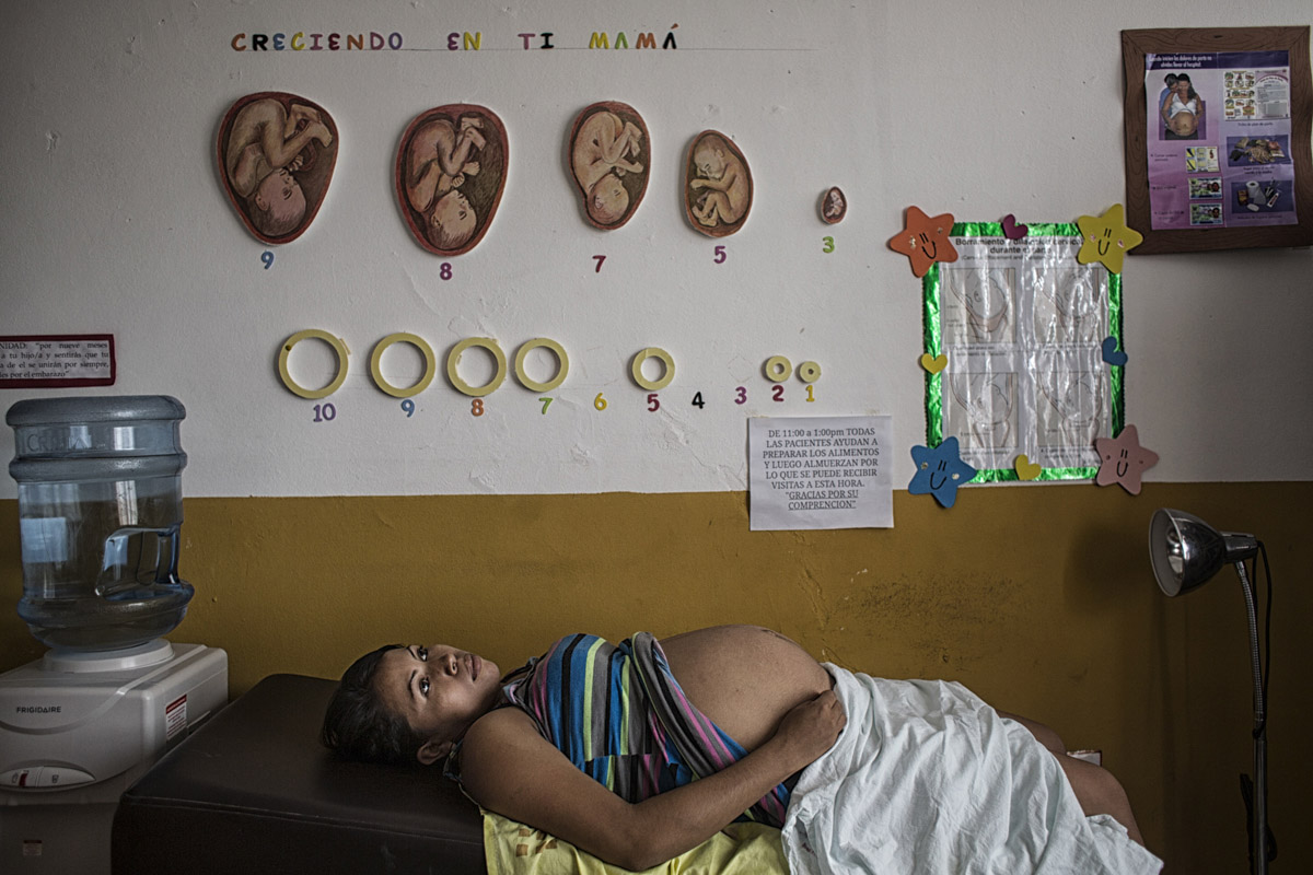 Planes de Renderos, El Salvador-May 2016: Abigail Sanches from San Luis Stalpa la Paz waiting to be examined at the maternal waiting house which especially helps women who come from areas without access to a nearby hospital wait out the end of the pregnancies in order to be close to a hospital and avoid complications. Pregnant women in today's El Salvador face a whole host of challenges from the threat of the mosquito born illness, Zika which has been linked to the grave condition of microcephaly in newborns, to the constant threat of gang violence with one of the highest murder rates in the world, to an increasing rape epidemic. However the most important threat to women's reproductive rights is by far the State's criminal ban on abortion. Doctors and nurses are trained to spy on women's uteruses in public hospitals, reporting any suspicious alteration to the authorities and provoking criminal charges which can lead to between 6 months to 7 years in prison. It is the poorer class of women who suffer the most as doctors in private hospitals are not required to report. Roughly 25 women are serving 30 to 40 year sentences on homicide charges for allegedly killing their newborn children. Although the women's stories, most of which resemble premature births or late term miscarigaes are often dismissed in trials, laced with moral accusations, based little on the consitution and scientific facts. ©Nadia Shira Cohen