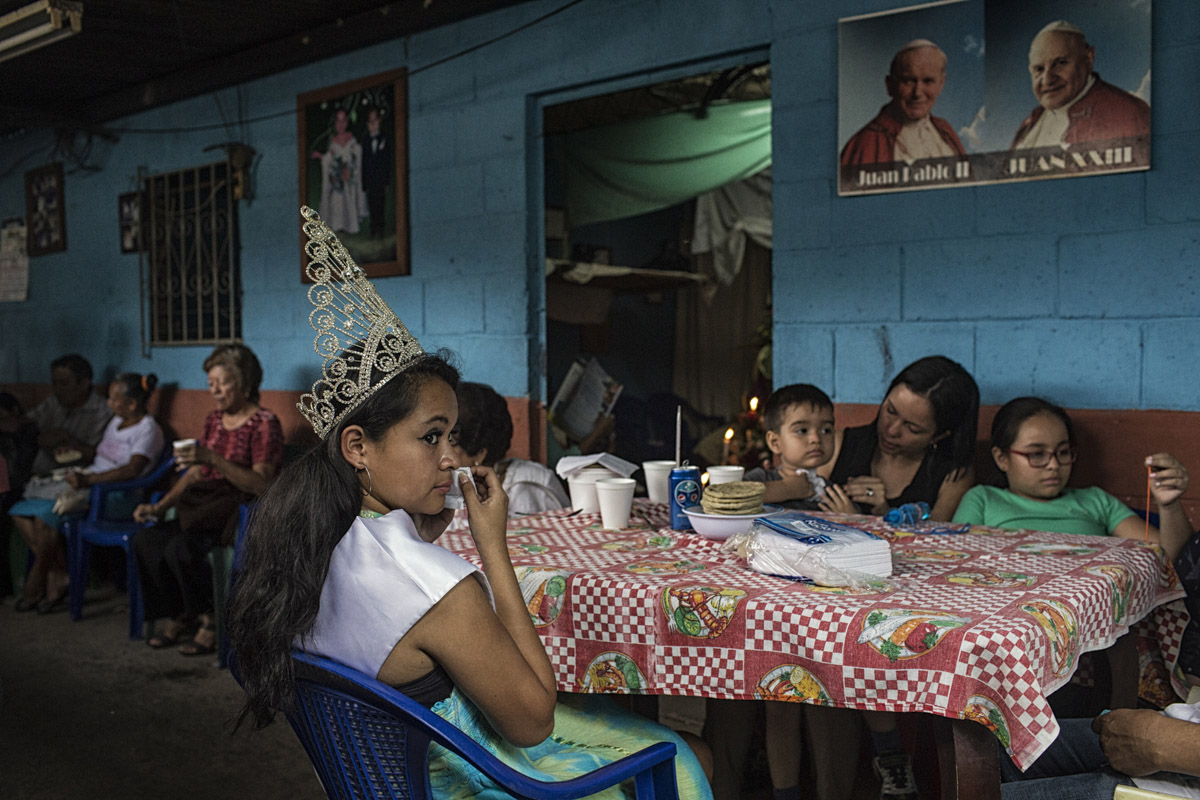 Panchmalco, El Salvador-May 2016: The queen of the annual Palms Festival eating lunch with the whole town at her home. The festival features a procession of the Virgin Mary through the town's narrow streets and attracts people from all over the country as well as internationally who come to idolize her. Young women such as her who live in gang controlled neighborhoods are under increasing risk of being raped and forced to date gang members. Pregnant women in today's El Salvador face a whole host of challenges from the threat of the mosquito born illness, Zika which has been linked to the grave condition of microcephaly in newborns, to the constant threat of gang violence with one of the highest murder rates in the world, to an increasing rape epidemic. However the most important threat to women's reproductive rights is by far the State's criminal ban on abortion. Doctors and nurses are trained to spy on women's uteruses in public hospitals, reporting any suspicious alteration to the authorities and provoking criminal charges which can lead to between 6 months to 7 years in prison. It is the poorer class of women who suffer the most as doctors in private hospitals are not required to report. Roughly 25 women are serving 30 to 40 year sentences on homicide charges for allegedly killing their newborn children. Although the women's stories, most of which resemble premature births or late term miscarigaes are often dismissed in trials, laced with moral accusations, based little on the consitution and scientific facts. ©Nadia Shira Cohen