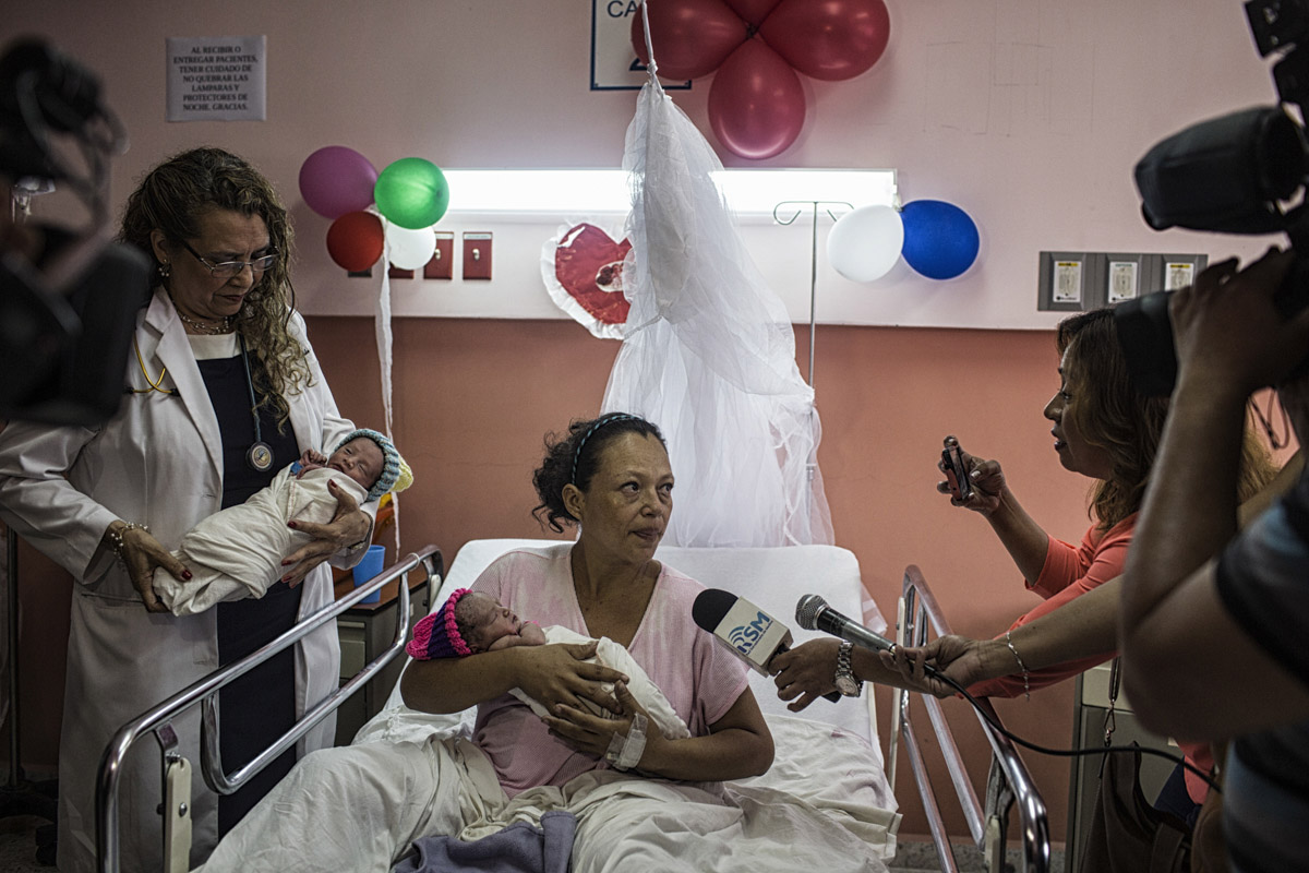 "San Salvador, El Salvador-May 2016: Dra. María Isabel Rodríguez, Director of the""Hospital Nacional de la Mujer"" in San Salvador congratulates Brenda Molina, 34 years old on her newly born twins, the second to be born on Mother's Day in the city. Pregnant women in today's El Salvador face a whole host of challenges from the threat of the mosquito born illness, Zika which has been linked to the grave condition of microcephaly in newborns, to the constant threat of gang violence with one of the highest murder rates in the world, to an increasing rape epidemic. However the most important threat to women's reproductive rights is by far the State's criminal ban on abortion. Doctors and nurses are trained to spy on women's uteruses in public hospitals, reporting any suspicious alteration to the authorities and provoking criminal charges which can lead to between 6 months to 7 years in prison. It is the poorer class of women who suffer the most as doctors in private hospitals are not required to report. Roughly 25 women are serving 30 to 40 year sentences on homicide charges for allegedly killing their newborn children. Although the women's stories, most of which resemble premature births or late term miscarigaes are often dismissed in trials, laced with moral accusations, based little on the consitution and scientific facts. ©Nadia Shira Cohen"