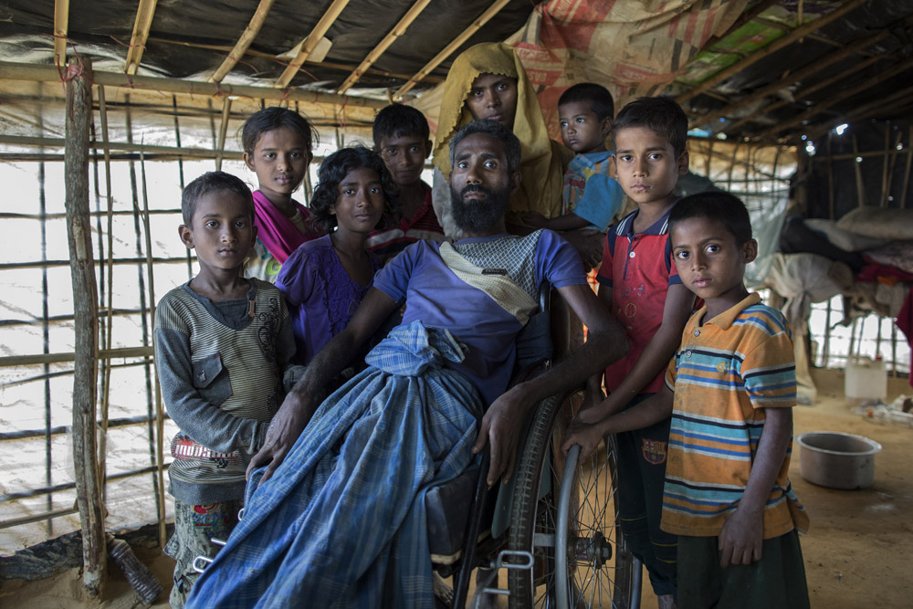A portrait of Mohammad Alamgir, 40, and his family. Mohammad disabled due to polio, fled with his family from recent violence in Myanmar, and has taken shelter in Kutupalong refugee camp, Cox's bazar.