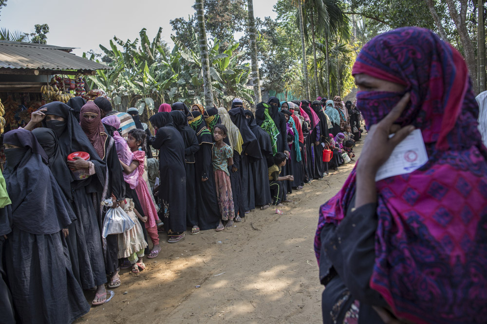 Rohingya refugees who recently fled from violence in Myanmar wait in a long food queue in Ukhia on March 5, 2017, Cox's Bazar.