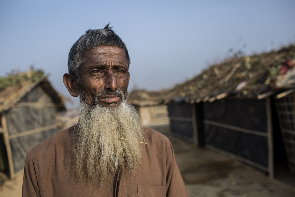Abdul Salam,65, who fled from violence in Myanmar, stands in front of his makeshift home in Kutupalong newly expanded Rohingya refugee camp.