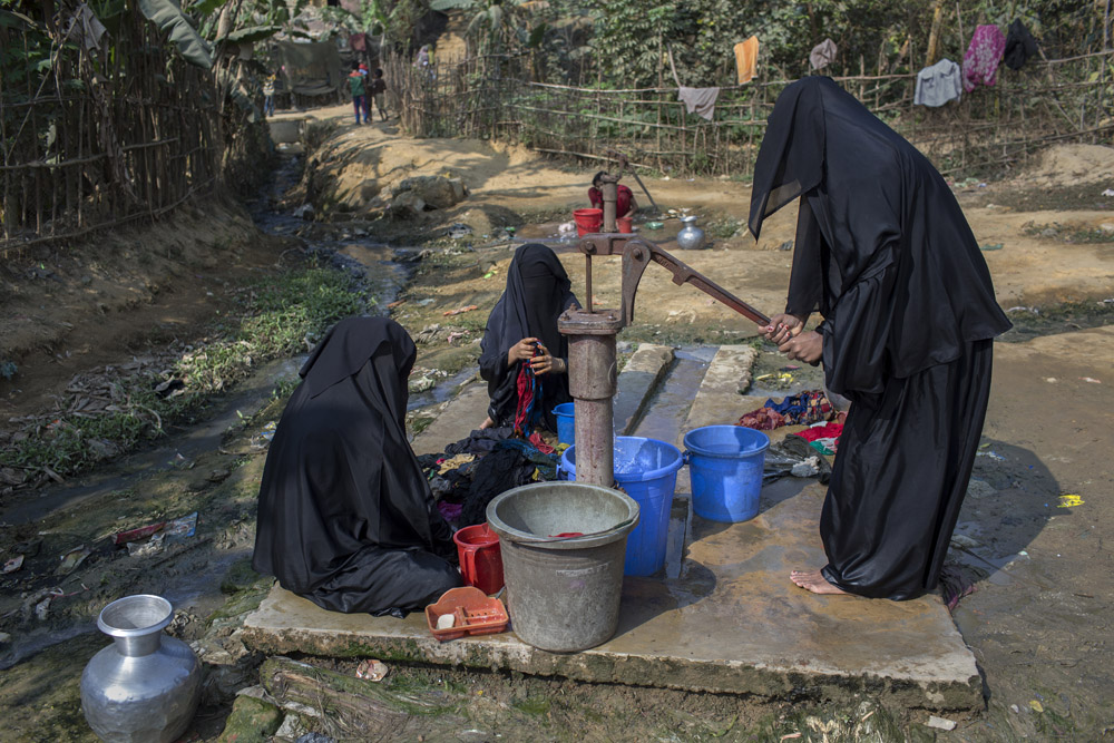 Rohingya women who fled from violence in Myanmar wash clothes in Kutupalong refugee cam, cox's bazar. They always wear hijab when go outside to work.