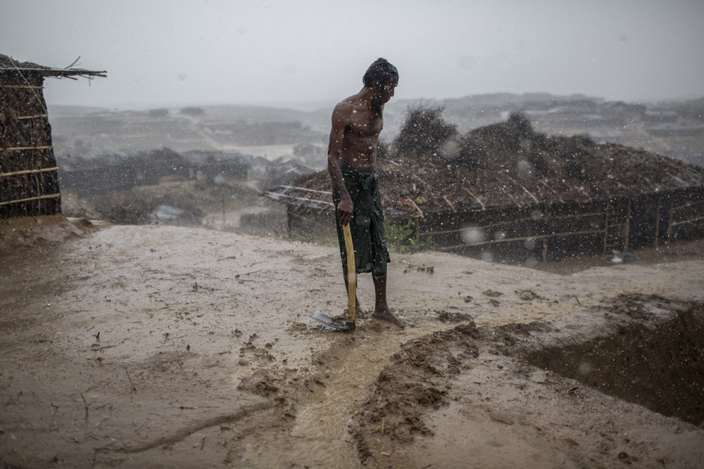 A Rohingya refugee tries to protect his makeshift home from the rain in Kutupalong newly expanded camp.