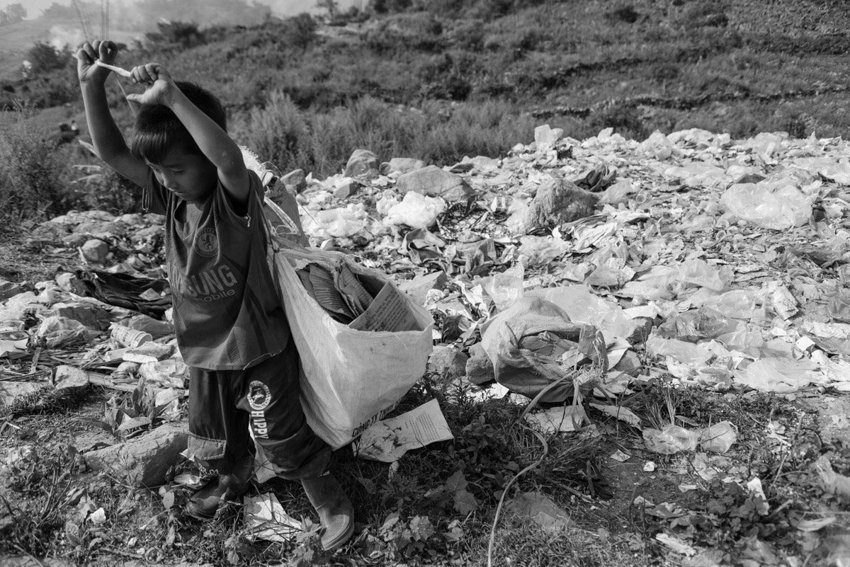 A boy collects paper trash in order to sell it for about one dollar per kilogram on a nearby market. This way he helps to support the family's income.