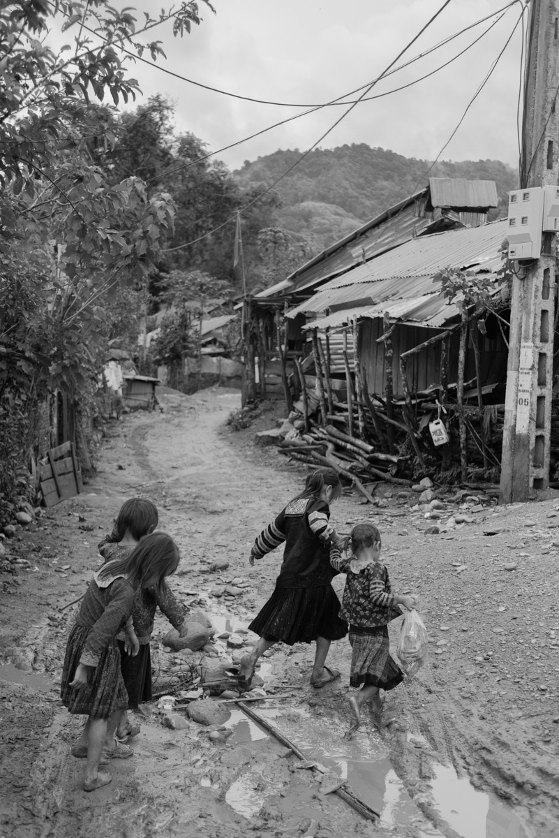 A group of girls is walking through a mudded street in their village after heavy rainfall.