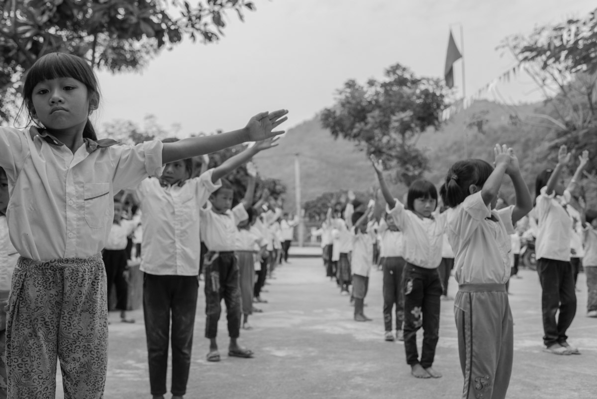 Children are performing to a Communist Party of Vietnam's song that is played every day at school. Most of the children do not understand the meaning as their mother tongue is not Vietnamese.