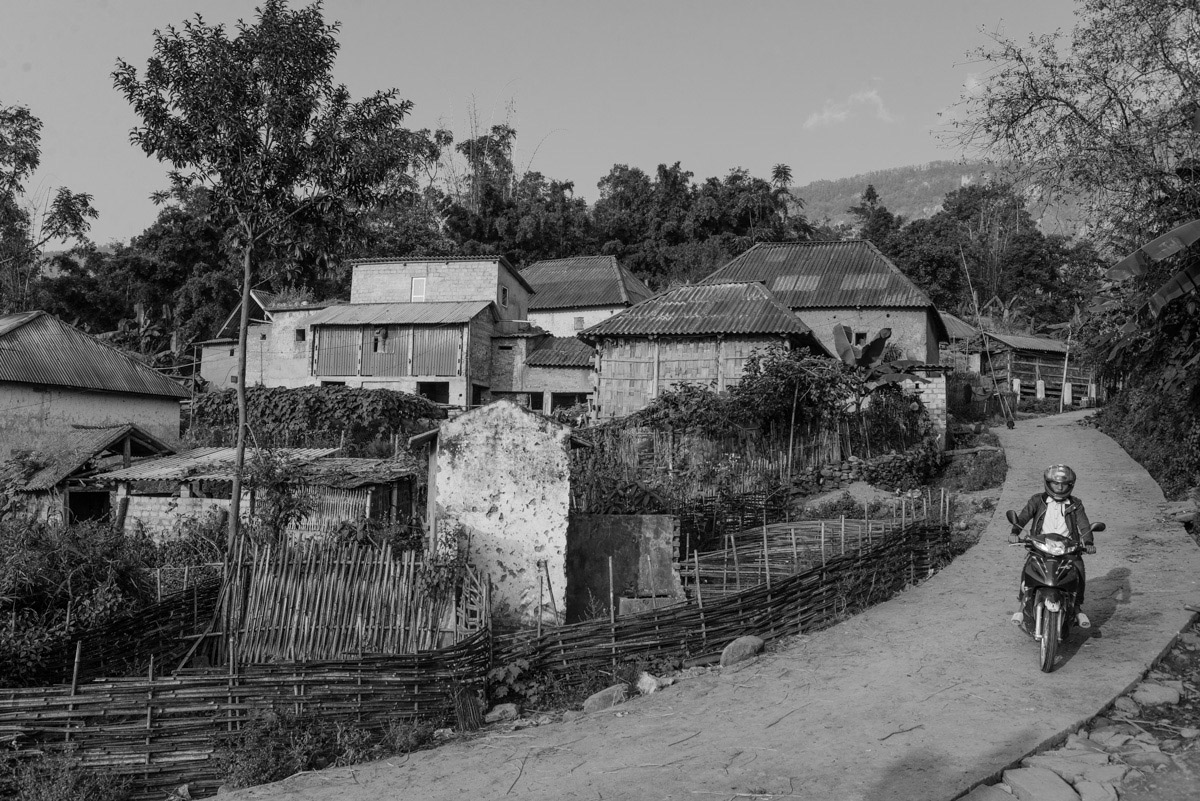 A man rides through his village on a motorbike. Motorbikes are necessary means of transportation and bridging the long distances between remote villages and towns along the mountains.