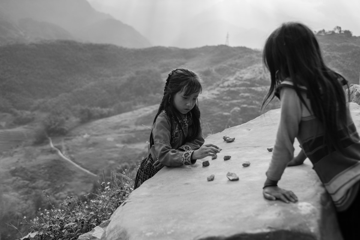 Girls are playing with stones on a self-made board.